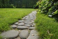 Weg von den Kopfsteinen in einem Gras in einem Garten stockfoto