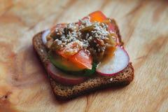 Weganin kanapka z avocado i warzywami na drewnianym tle Zdjęcia Stock