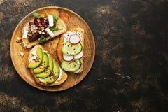 Weganin zdrowe kanapki z avocado, arugula beetroot, ogórka, rzodkwi i feta serem na ciemnym grunge tle, Odgórny widok, kopia zdjęcie royalty free