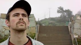 Wege des jungen Mannes im Regen blickt in Richtung des Himmels stock video