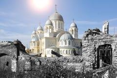 Wegen der Ruinen des defekten Gebäudes, steigt der orthodoxe Tempel mit vielen goldenen Hauben mit Kreuzen majestätisch lizenzfreie stockbilder