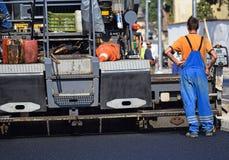 Wegenbouw met een asfalt het bedekken voertuig Stock Foto
