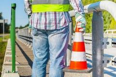 Wegenbouwarbeider met verkeerskegel dichtbij weg Stock Foto's