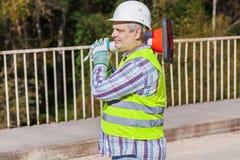 Wegenbouwarbeider met verkeerskegel op de brug Royalty-vrije Stock Afbeeldingen