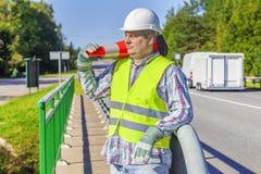 Wegenbouwarbeider met verkeerskegel op schouder dichtbij weg Stock Afbeeldingen