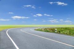 Wegenkromme met groene gras blauwe hemel en wolkenachtergrond Royalty-vrije Stock Foto's