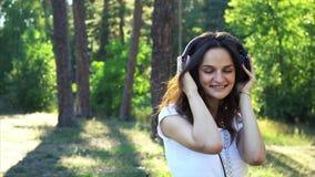 Weggegaane vrouw die in hoofdtelefoons aan de muziek luisteren stock footage