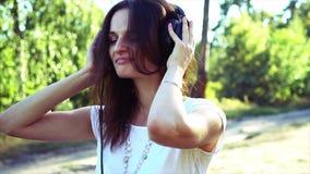Weggegaane vrouw die in hoofdtelefoons aan de muziek luisteren stock videobeelden