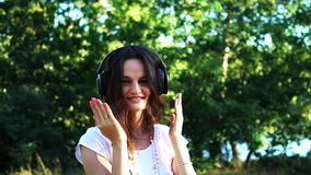 Weggegaane vrouw die in hoofdtelefoons aan de muziek luisteren stock video