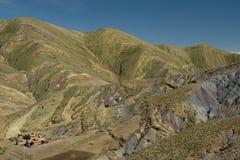 Weggeschoten groene en regenboogbergen in Maragua-Krater Bolivië met landbouwbedrijfhuizen royalty-vrije stock afbeelding