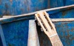 Weggeworfene alte Gitarre und Müllcontainer Stockbild