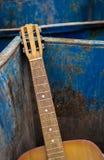 Weggeworfene alte Gitarre und Müllcontainer Stockfotos