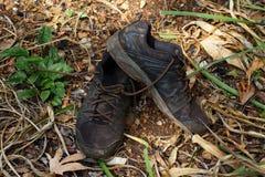 Weggeworfene schäbige schwarze Schuhe stockbilder