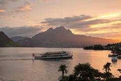 Weggis Schweiz - September 15, 2017: Sikt av sjön Lucerne och monteringen Pilatus på solnedgången, med ett fartyg i förgrunden arkivbild