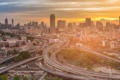 Wegkruising met de bureaubouw stad de stad in met zonsonderganghemel Stock Foto's