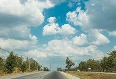 Wegreis aan uit stad met lijnen van groene bomen en aardige wolken blauwe hemel in de zomer Stock Afbeelding