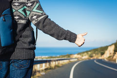 Wegreis, reis, gebaar en mensenconcept - lifter die auto met duimen op handteken tegenhouden Stock Afbeelding