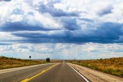 Wegreis - Twee steegweg op de vlaktesrek rechtstreeks over horizonunder dramatische hemel met vreemd licht stock afbeeldingen