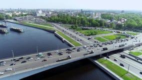 Wegverbinding op verscheidene niveaus op dichtbij blauwe rivier met brug en aken stock video