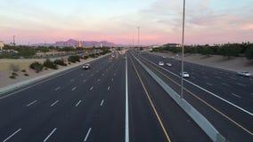 Wegverkeer bij zonsondergang aan nacht, Arizona, de V.S.