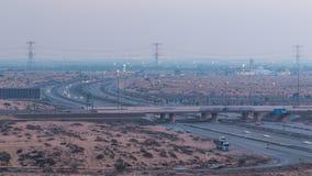 Wegwegen met verkeersdag aan nacht timelapse in een grote stad van Ajman aan Doubai vóór zonsondergang Het concept van het vervoe Royalty-vrije Stock Afbeeldingen