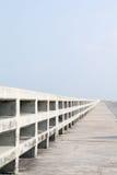 Wegweise auf Brücke über dem Meer Stockbilder