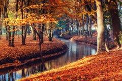 Wegweisenbrücke über Fluss mit bunten Bäumen in der Herbstzeit Stockfoto