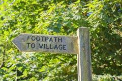Wegweiser mit Fußweg zum Dorf stockfotos