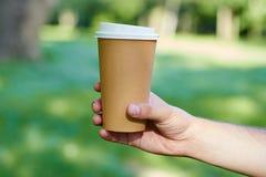 Wegwerfkaffeetasse auf Tabelle auf der Hand des Mannes Stockfotografie