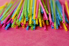 Wegwerfplastikstrohe des bunten einzelnen Gebrauches auf rosa Oberfläche lizenzfreies stockbild