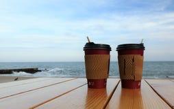 Wegwerftasse kaffees, die auf einer Tabelle gegen das blaue Meer stehen Kaffeetasse auf hölzerne Tischplatte auf blauem Meer des  stockfotografie