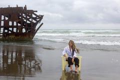 Wehmütige Frau auf Strand mit Schiffbruch Lizenzfreie Stockfotografie