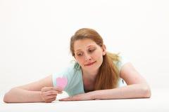 Wehmütige Frau, die Valentinsgrußinneres betrachtet Lizenzfreies Stockfoto