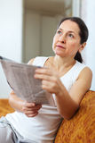 Wehmütige Frau mit Zeitung Stockfoto