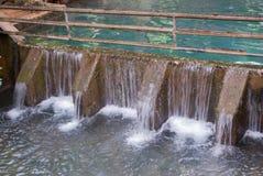 Wehr oder kleine Verdammung mit Wasserfall im Wald Stockfoto
