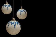 Weiß-blaue glänzende Weihnachtskugeln auf einer Schwarzrückseite Lizenzfreie Stockfotografie