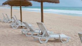 Weiß entspannt sich Stühle im Strand nah an Ozean stock video footage