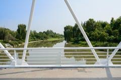 Weiß-gemalte Leitschiene und Binder der Brücke über Fluss im sunn stockfoto