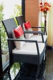 Weiß gepolsterter Stuhl im Wohnzimmer mit Blumen Lizenzfreie Stockbilder
