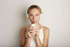 Weiß-Hintergrund des Porträt-hübscher junge Frauen-hörender Musik-Spieler-Kopfhörer-freien Raumes Hübsches Mädchen, das Coffe hal Lizenzfreie Stockfotografie