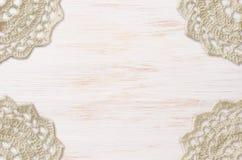 Weiß malte hölzernes Brett und eine Häkelarbeit Doilies in den Ecken Stockbild