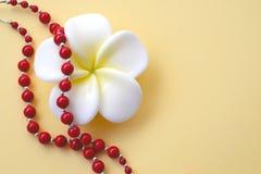 Weiß mit gelber Blume und hellen roten korallenroten Perlen mit silbernen Akzenten auf einem gelben Hintergrund stockfoto