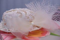 Weiß stickte den Hut, der auf einem blumigen Stoff, ein altmodischer Frauen ` s Hochzeitszusatz stillsteht stockfotografie