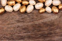 Weiß und Gold-Osterei übersteigen Grenze über rustikalem Holz Stockfoto