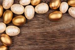 Weiß und Gold-Osterei bringen Grenze über rustikalem Holz in Verlegenheit Stockbild