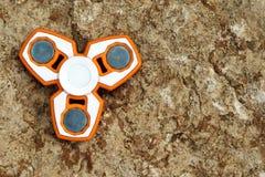 Weiß und orange Unruhe SPINNER-Druckentlastungsspielzeug auf Steinba Stockbilder