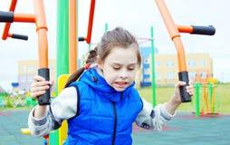 Weiß zehn Jahre alte Mädchen, die Übungen auf Sportsimulatoren auf einem Sportplatz tun Stockbilder