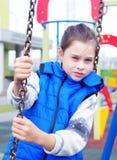 Weiß zehn Jahre alte Mädchen hat einen Rest auf einem Schwingen am Spielplatz Stockfotos