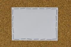 Weißbuch befestigt auf dem braunen Brett mit Hefter Lizenzfreie Stockbilder