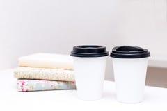 Weißbuch cupsa Nd ein Stapel Bücher, die auf einer weißen Tabelle stehen Stockfoto
